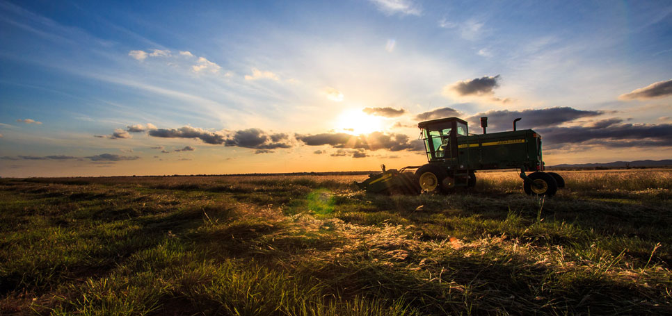 The sun sets over a tractor in a southwestern Oklahoma field.